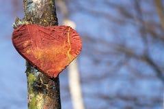 Vieux coeur en bois sur le ciel bleu d'arbre et le fond de forêt Forme rouge de symbole d'amour texturisée dehors Photo libre de droits