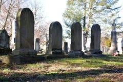 Vieux contre-jour de pierres tombales le jour en retard d'hiver Photographie stock libre de droits