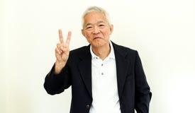 Vieux costume occasionnel asiatique d'homme supérieur avec le visage et la main heureux g Image stock