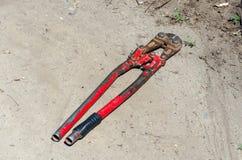 Vieux coupeur rouge de vue supérieure pour le fil ou les barres d'acier sur la terre image stock