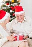 Vieux couples échangeant des cadeaux de Noël Images stock