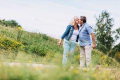 Vieux couples embrassant sur une promenade Photos stock