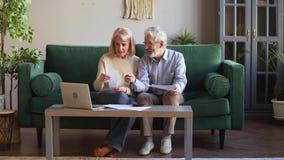 Vieux couples heureux calculant les factures domestiques à la maison avec l'ordinateur portable banque de vidéos