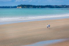 Vieux couples marchant le long d'une plage photos stock