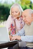Vieux couples utilisant l'ordinateur portatif Photographie stock