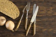 Vieux couverts, un morceau de pain de seigle et oignons Photo stock