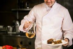 Vieux cuisinier principal dans les clothers blancs tenant le pot de pétrole et de plat avec le plat savoureux Images stock