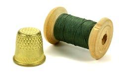 Vieux dé en laiton et la bobine des fils pour coudre sur un fond blanc Image libre de droits