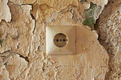 Vieux débouché électrique sur le mur décrépit Photo stock