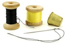 Vieux dés en laiton, bobine avec des fils et une aiguille pour coudre sur un fond blanc Photo stock