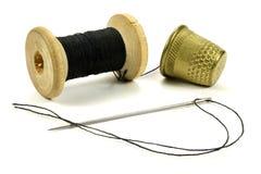 Vieux dés en laiton, bobine avec des fils et une aiguille pour coudre sur un fond blanc Image stock