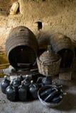 Vieux dames - jeannes ont vieilli des bouteilles de vin et des barils en bois dans un sous-sol Images libres de droits