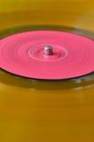 Vieux disque vinyle coloré jaune-orange Fond Images libres de droits