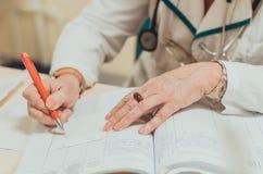 Vieux docteur expérimenté féminin écrivant une prescription médicale photographie stock libre de droits