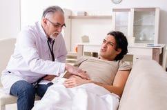 Vieux docteur masculin rendant visite au jeune patient masculin photos libres de droits