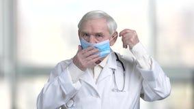 Vieux docteur mettant sur le masque médical bleu banque de vidéos
