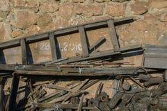 Vieux escalier, bâtons et puces en bois sur l'arrière-cour sous le fond de mur en pierre de maison Image stock