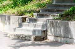 Vieux escaliers concrets d?truits en parc, dalles en b?ton, margelle, herbe verte, arbres photo stock