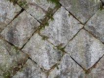 Vieux et carrés blocs en pierre avec de la mousse et le sol dans les lacunes entre image libre de droits