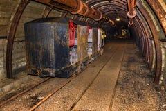 Vieux et rouillé train de mine pour le transfert de personnel garé dans le tunnel de mine avec le boisage en bois photos libres de droits