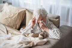 Vieux femelle épuisé ayant la migraine dans la chambre à coucher Photo stock