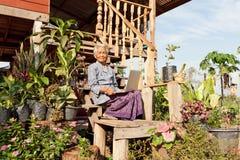 Vieux femme asiatique avec l'ordinateur portatif Image libre de droits