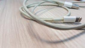 Vieux fil futé de chargeur de téléphone sur le plancher en stratifié Image stock