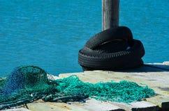 Vieux filets de pêche et pneus sur le dock Photographie stock