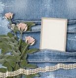 Vieux fond de denim avec le cadre de papier, perles Photo stock