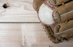 Vieux gant de base-ball en cuir porté et boule utilisée sur un en bois Photo libre de droits