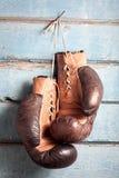Vieux gants de boxe avec un lacet au-dessus de mur bleu Images stock