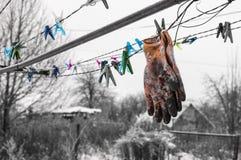 Vieux gants sales accrochant sur le dessiccateur de rue photographie stock libre de droits