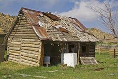 Vieux garage de grange de logarithme naturel chargé avec la camelote Photos libres de droits