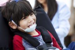 Vieux garçon handicapé de cinq ans heureux dans le fauteuil roulant Photos stock