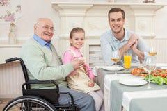 Vieux grand-père handicapé gai avec sa famille photos libres de droits