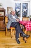 Vieux grand-père s'asseyant avec son bâton de marche à la table image libre de droits