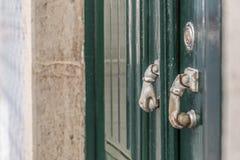 Vieux heurtoirs de porte de main en métal sur la porte verte photo libre de droits