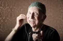 Vieux Hiptser écoutant le dispositif sonore tenu dans la main Images stock