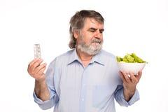 Vieux hommes avec une cuvette de salade et de pilules Photo stock