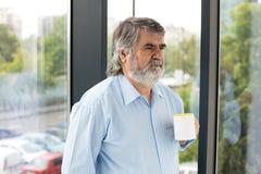 Vieux hommes avec une tasse de café à côté d'une fenêtre Images stock