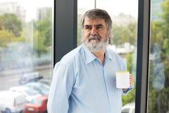 Vieux hommes avec une tasse de café à côté d'une fenêtre Photo libre de droits