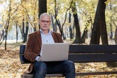 Vieux hommes d'affaires travaillant à l'ordinateur portable dehors sur un banc Photos libres de droits
