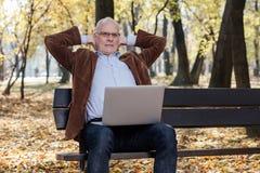 Vieux hommes d'affaires travaillant à l'ordinateur portable dehors sur un banc Images libres de droits