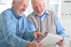 Vieux hommes lisant un journal Photos stock