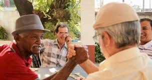 Vieux hommes se serrant la main gagnant le jeu du domino Image stock