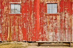 Vieux hublots rouges de grange et banc isolé Images libres de droits