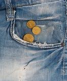 Vieux jeans avec des pièces de monnaie dans la poche Image stock