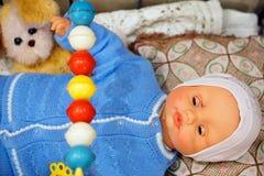 Vieux jouet, poupée de cru - bébé dans un chandail bleu dans une huche avec un chien images libres de droits