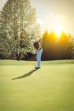 Vieux joueur de golf mettant sur le vert Photos libres de droits