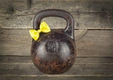 Vieux kettlebell avec un arc jaune de lien sur un fond en bois Images libres de droits